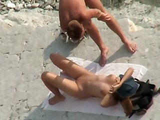 A hotter couple relaxes on a nudist beach